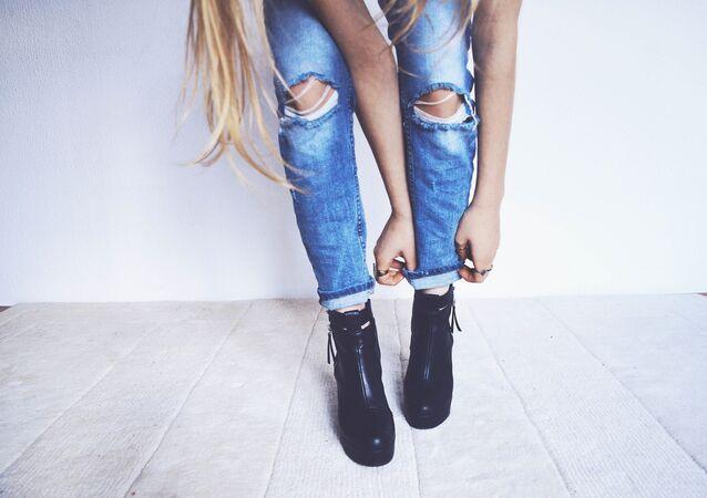 Mulher vestindo jeans rasgados