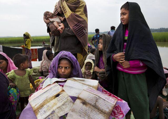 Mulher rohingya, em fuga de Mianmar para o Bangladesh, seca seus documentos na fronteira entre os dois países