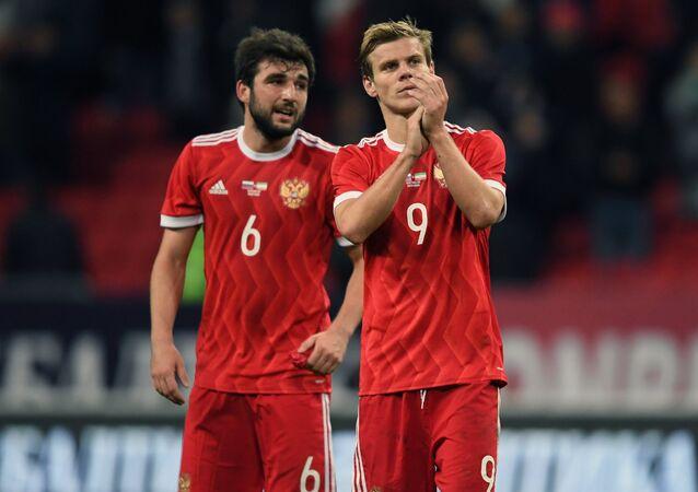 Jogadores Georgi Dzhikiya e Aleksandr Kokorin da seleção russa agradecem sua torcida após uma partida com Irã
