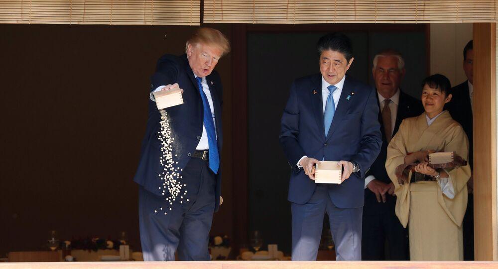 Presidente dos EUA, Donald Trump, e o premiê do Japão, Shinzo Abe, alimentando carpas no Palácio Akasaka, Tóquio