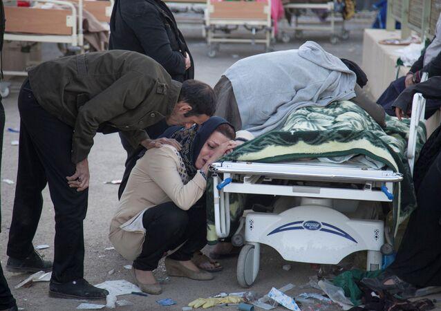 Mulher chorando junto a corpo de familiar após terremoto na província de Kermanshah, Irã
