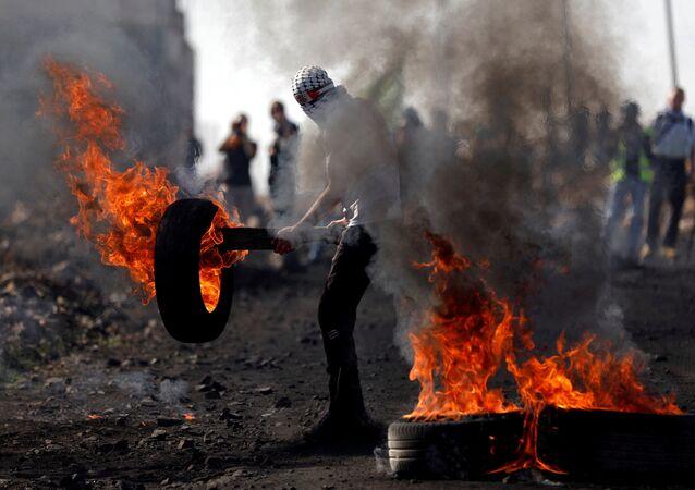 Palestino mascarado segurando um pneu em chamas durante confrontos com tropas israelenses em uma aldeia na Cisjordânia, 10 de novembro de 2017