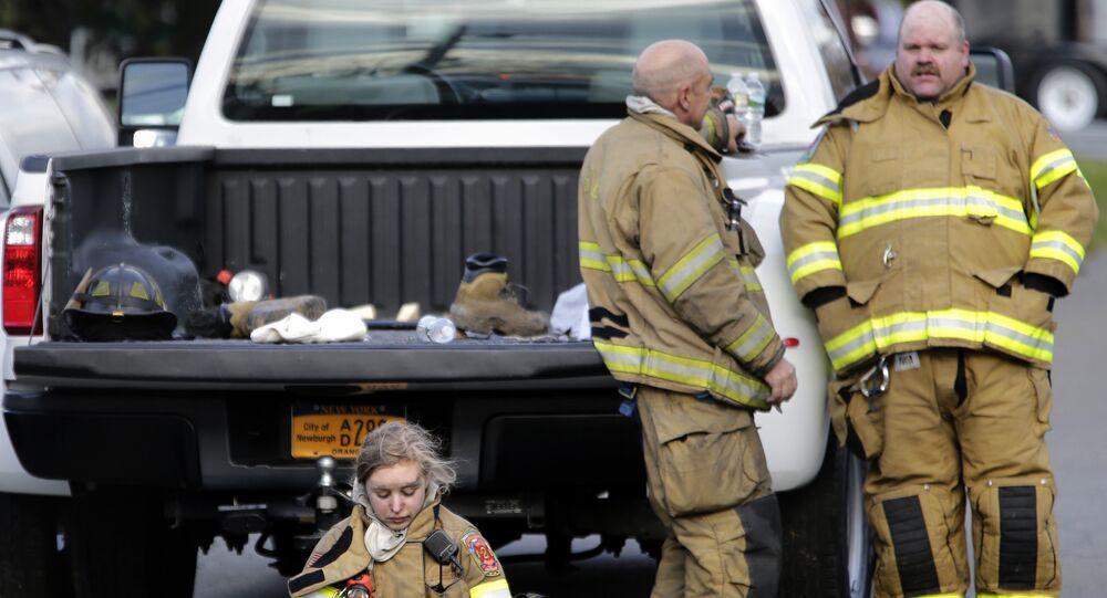 Bombeiros descansam enquanto trabalham para combater chamas em fábrica de New Windsor, NY