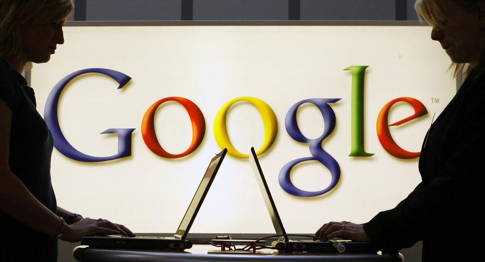 Pessoas trabalhando em notebooks em frente ao símbolo do Google em Hanover, Alemanha (foto de arquivo)