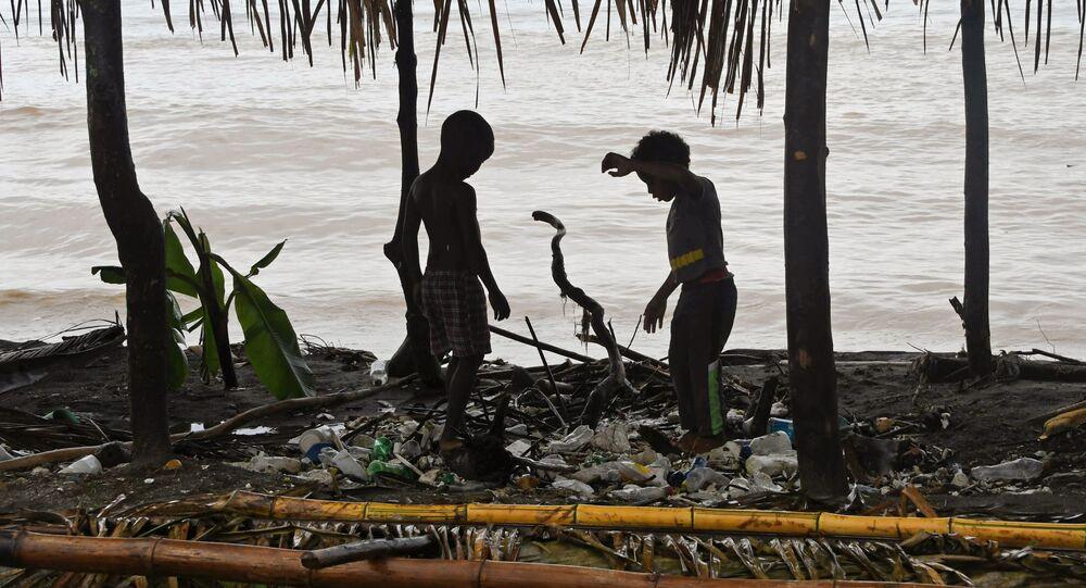 Crianças brincando no meio do lixo na praia de Omoa, Honduras