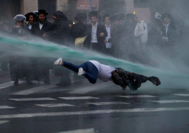 Pedestre é atingida por canhão d'água durante manifestação de judeus ortodoxos em Jerusalém