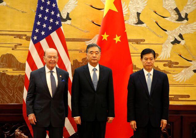 Secretário de Comércio dos EUA, Wilbur Ross, vice-premiê da China, Wang Yang, e ministro de Comércio chinês, Zhong Shan, com as bandeiras nacionais em fundo, Pequim, 8 de novembro de 2017