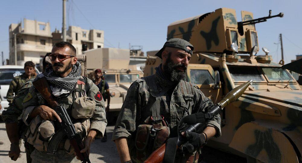 Combatentes das Forças Democráticas da Síria com armas nas mãos perto de veículos militares em Raqqa, Síria